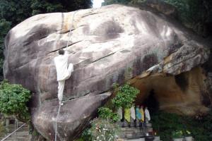 人面岩に上る住職
